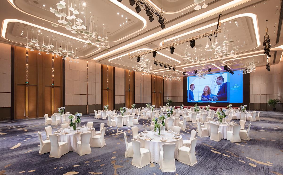 鲁能大宴会厅圆桌摆台,宴会厅装饰风格豪华而现代-济南鲁能希尔顿酒店